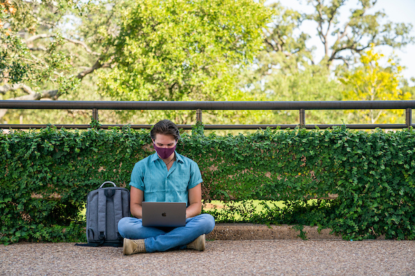 male student with mask sitting outside on the ground with his laptop on his lap